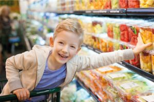 Child in Supermarket trolly reaching for pot of fruit
